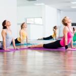 Four girls practicing yoga, Bhujangasana / Cobra Pose